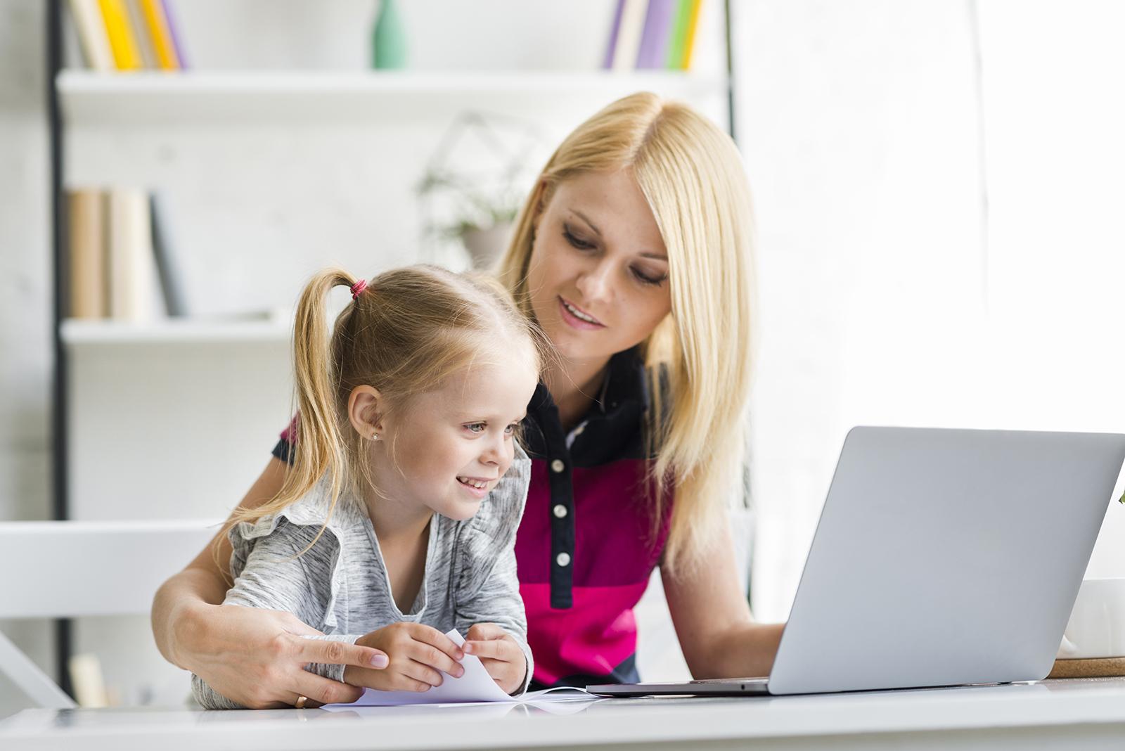 Home office-ból dolgozó anyuka, mellette a kislánya.