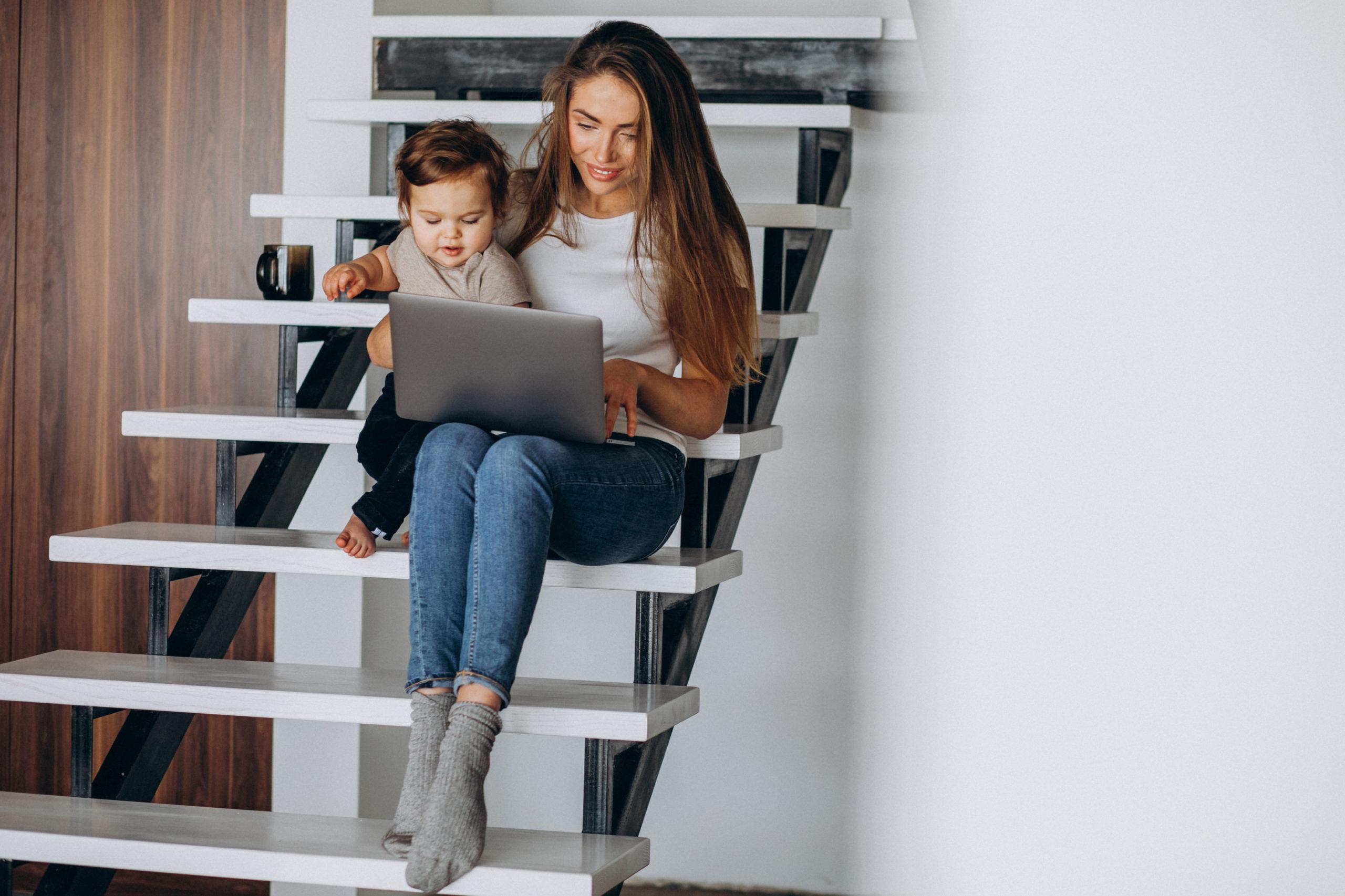 Egy fotó egy rugalmas munkarendben dolgozó anyukáról, gyermekével az ölében.