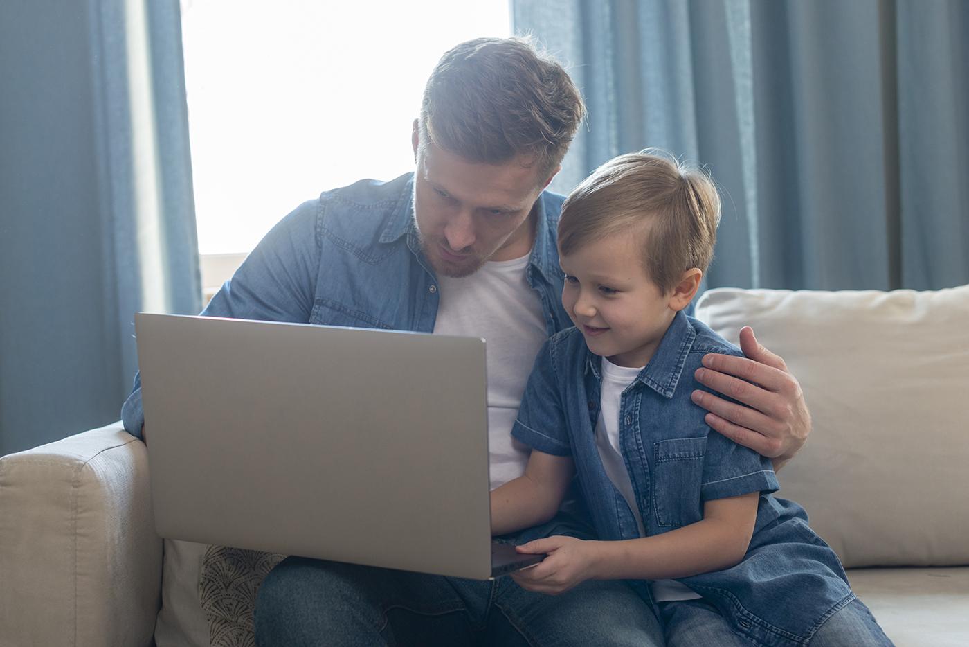 Apuka a laptopjánál ülve dolgozik, mellette a fia. Nem véletlen a képválasztás: GYED-et a férfiak is igényelhetnek.